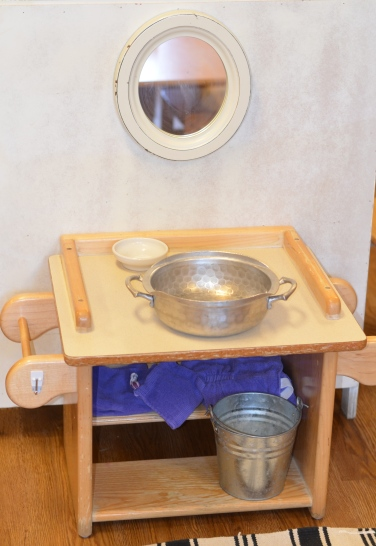 Our hand washing work includes water basin, bar of soap and soap dish, bucket, apron and cloths, and a low set mirror at the child's eye level