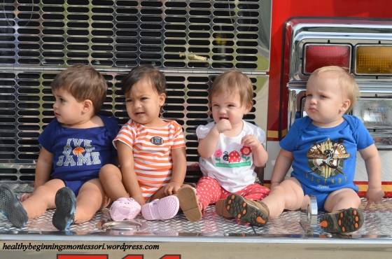 Our littlest friends enjoying the view from the front of the fire truck. (They were concentrating on the firemen's suits)